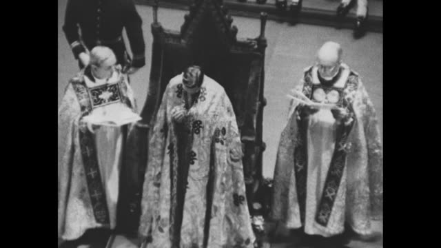 montage dean of westminster drapes armill around king george vi's neck during coronation ceremony at westminster abbey and drapes a gold royal robe... - coronation stock videos and b-roll footage