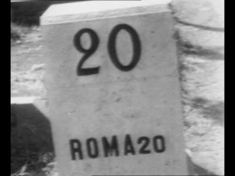 montage distance markers indicate travel progress toward rome / 20 km marker; pan to us tank and jeep moving away toward rome during world war ii /... - forze armate statunitensi video stock e b–roll