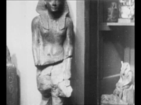 Montage exhibit of artifacts from King Tut's tomb includes large statues and small figures / three people stand near entrance to pyramid pan others...