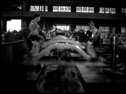 Montage, factory floor, cars being assembled.
