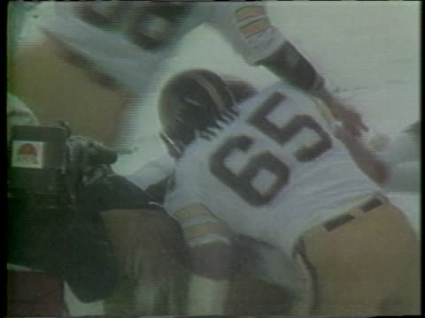 1983 montage ms ws football players from various usfl teams celebrating goal points by dancing, hugging, backflipping, giving high-fives, and spiking ball during games / usa - バク転点の映像素材/bロール