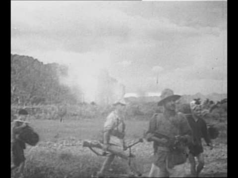 montage french soldiers carry wounded soldiers during first indochina war / french soldiers walk, with vietnamese people carrying supplies / soldiers... - other stock videos & royalty-free footage