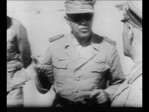 vídeos de stock, filmes e b-roll de montage german field marshal erwin rommel decars in african desert speaks to officers during world war ii / german hands shell up to soldier standing... - wehrmacht