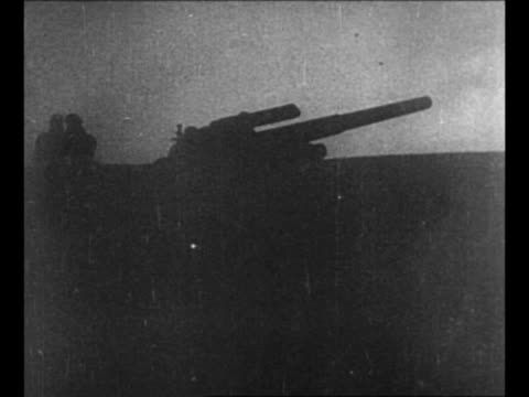 Montage German tanks move across terrain in World War II / montage artillery antiaircraft guns fire / montage soldiers shoot machine gun / rear shot...