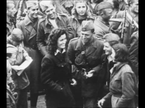 stockvideo's en b-roll-footage met montage group of male and female yugoslav partisans stand in street chat / montage armed partisan troops walk in streets of town in yugoslavia / from... - joegoslavië