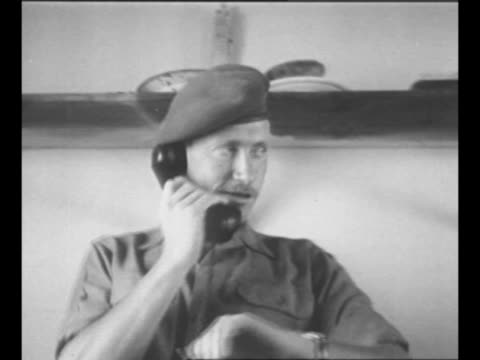 montage haganah officer talks on telephone while looking at his watch / shell of building used as haganah outpost with soldier on top / montage three... - 1948 stock-videos und b-roll-filmmaterial