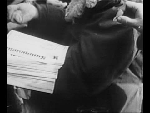 vídeos de stock, filmes e b-roll de montage helsinki citizens purchase and read copies of bulletin on snowy street document concerns the end of the winter war and the ensuing treaty /... - paramount building
