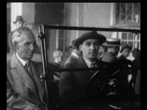 montage henry ford and son edsel sit in a new ford car marked fifteen millionth drive it down a small track / the newest model t stands with the... - 1927 bildbanksvideor och videomaterial från bakom kulisserna