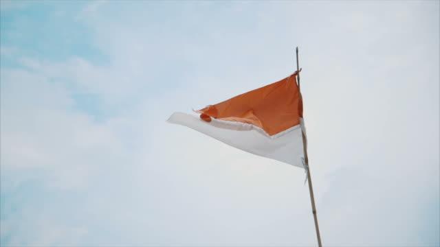 montaggio-bandiera dell'indonesia, a mezzogiorno e tramonto - mezzogiorno video stock e b–roll