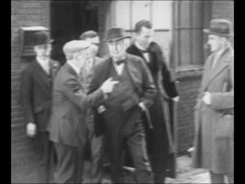 Montage inventor Thomas Edison stands at doorway outside of building shakes hands and speaks with men passing by / man in shirtsleeves smoking pipe...