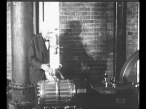 Montage inventor Thomas Edison with man in his lab with beaker and with machine / sheets of images move in Edison's invention the Kinetoscope / scene...