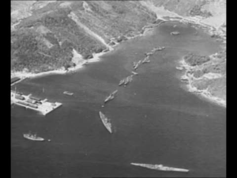 montage japanese submarines sail in single file out of channel toward sea / rear shot two men look out toward a submarine, with another submarine in... - torpedo stock videos & royalty-free footage