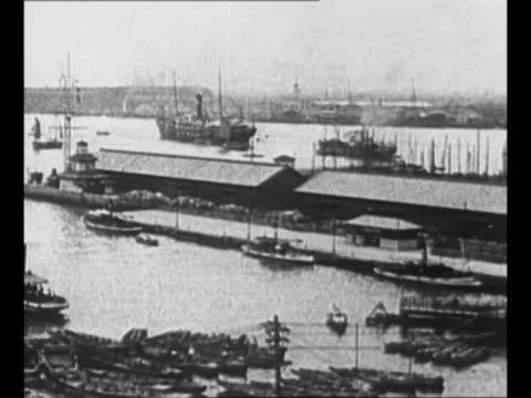 montage japanese town in early 1920s with residential area and harbor with boats temple area with pedestrians possibly yokohama / ws bicyclists and... - narrow stock videos & royalty-free footage