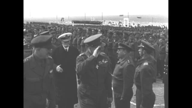 Montage King Paul and Queen Frederica inspect Greek troops on island of Makronisos / pan troops stand at ease / montage excited troops carry King...