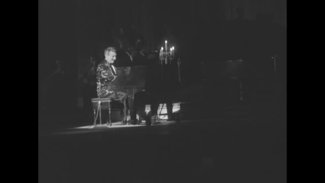 Montage Liberace animatedly plays grand piano on stage and in spotlight / side shot Liberace rises from piano bench walks to front of stage and bows...