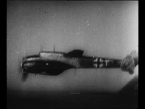 Montage Luftwaffe planes fly during WWII air battle / Allied plane probably B24 approaches emitting smoke from gunfire / plane spews fire starts to...