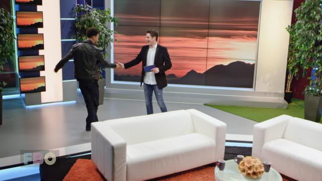montage: männliche talkshow-moderator seine männliche stargast, der einen tanz beim händeschütteln begrüßen - moderator stock-videos und b-roll-filmmaterial