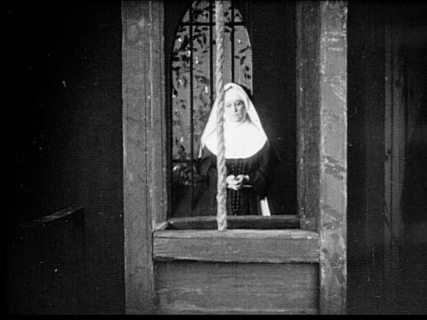 1916 b/w montage medium shot - close-up nun pulling rope in belfry/ church bell ringing side to side - 1916 stock videos & royalty-free footage