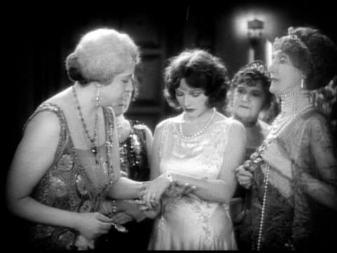 1928 b/w montage - medium shot group of older women talking to younger woman and admiring her bracelet / woman replying 'a wedding present from richard.' / usa  - 1928 stock videos & royalty-free footage