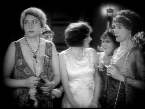 1928 b/w montage - medium shot group of older women talking to younger woman and admiring her dress / woman replying 'a wedding present from richard.' / usa  - 1928 stock videos & royalty-free footage