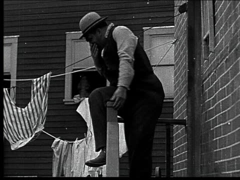 1918 b/w montage medium shot man nearly falling off railing/ medium shot cop throttling man before man runs up stairs - oliver hardy stock videos & royalty-free footage