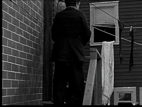 1918 b/w montage medium shot man throwing brick from steps/ wide shot man in alley stumbling as brick hits ground - oliver hardy stock videos & royalty-free footage