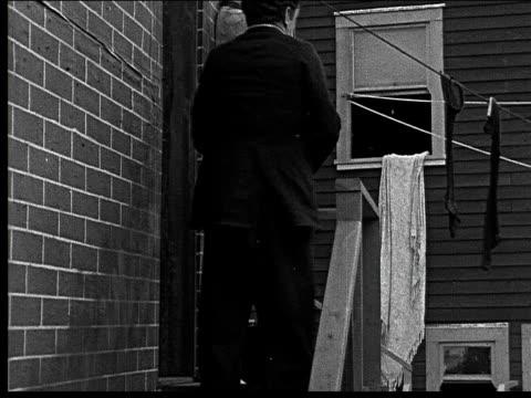 vidéos et rushes de 1918 b/w montage medium shot man throwing brick from steps/ wide shot man in alley stumbling as brick hits ground - trébucher