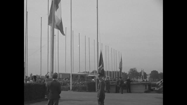 montage men raise french and british flags on poles in munich in advance of conference there - bandiera del regno unito video stock e b–roll