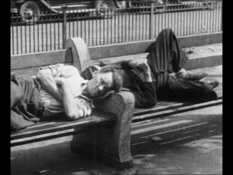 montage men sit on park benches and chat sleep on park benches during the great depression / elderly couple listens to radio set / montage cu... - 失業点の映像素材/bロール
