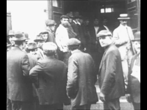 vídeos de stock, filmes e b-roll de montage men stand in line outside draft board building to register for world war i military service as other men exit after registering / man seated... - título de eleitor