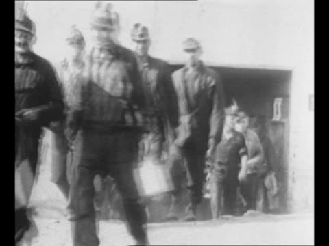 vidéos et rushes de montage miners leave mine shafts some carry lunch pails / miners with coal cars / pan group of anthracite coal miners poses for photo outside mine in... - mineur de charbon