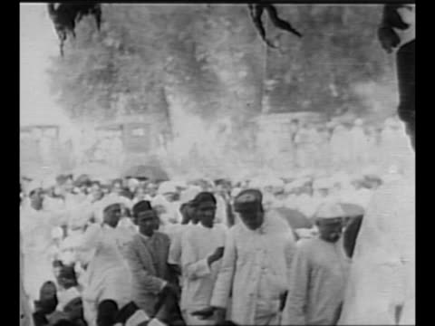 stockvideo's en b-roll-footage met montage mohandas k. gandhi sits with group of followers at sabarmati ashram, one of his residences / gandhi and followers walk past camera en route... - mahatma gandhi