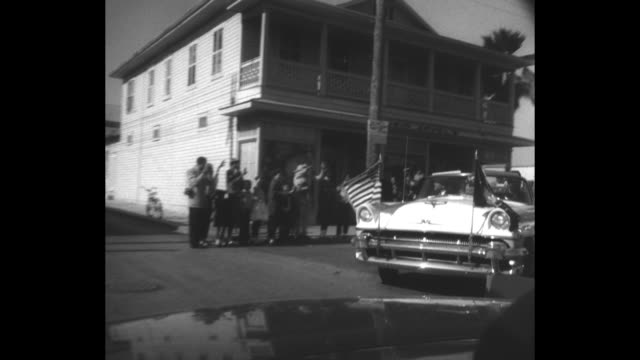 vídeos de stock, filmes e b-roll de pov montage motorcade led by car with us flag and flag with us presidential seal drives on key west street as spectators along street watch and wave... - columbine