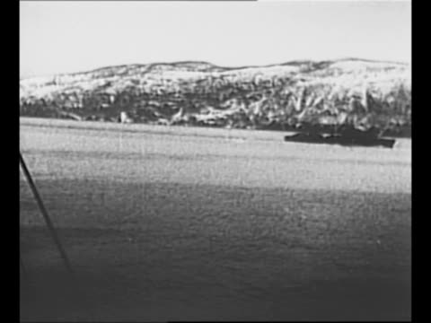 Montage naval guns fire during battle at Narvik fjord during World War II / montage torpedoes launch into ocean / WS British destroyer H99 in harbor...