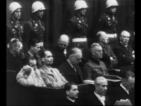 montage nazi defendants in prisoner's dock with military police standing behind at nuremberg trials / rear shot us supreme court justice robert h... - gerichtsverhandlung stock-videos und b-roll-filmmaterial