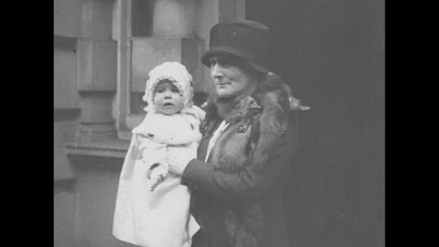 montage nurse holds baby princess elizabeth as she stands in doorway of building then walks outdoors princess elizabeth bundled up in coat and hat... - famiglia reale video stock e b–roll