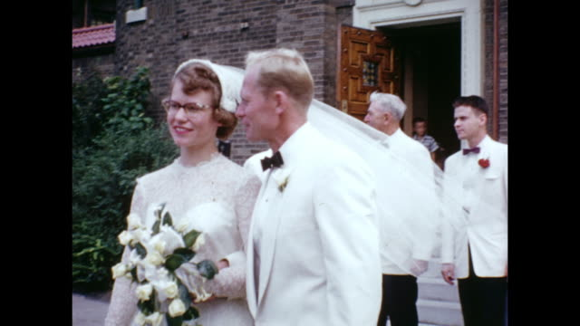 a montage of a bride and groom leaving a church after getting married. rice is thrown by friends and family. - 1950 stock-videos und b-roll-filmmaterial