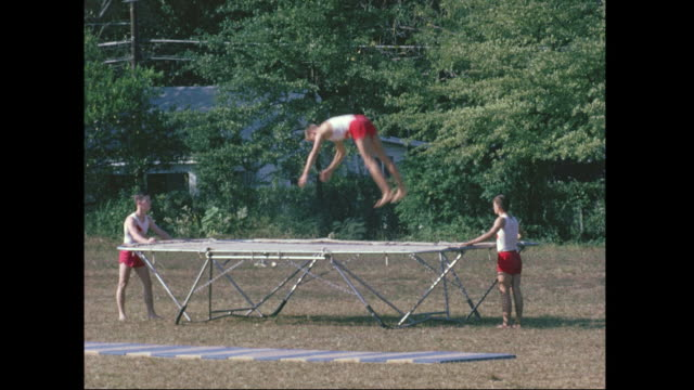 montage of a competative student trampoline team jumping on a trampoline outdoors on a sunny day. - トランポリン点の映像素材/bロール