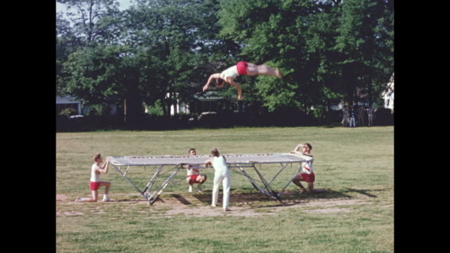 stockvideo's en b-roll-footage met montage of a competative student trampoline team jumping on a trampoline outdoors on a sunny day. - trampoline