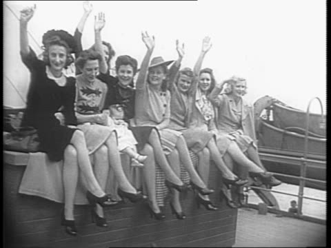 Montage of a group of 296 women most holding babies aboard a ship from Australia wave to camera / two woman speak about their American husbands