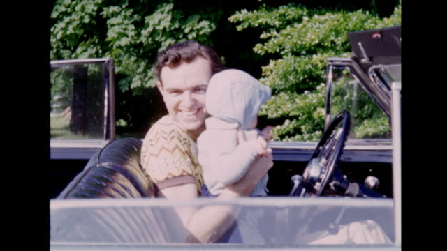 a montage of a man driving up and getting out of his 1948 buick with his baby girl. - husband stock videos & royalty-free footage