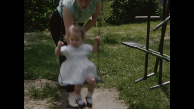 vidéos et rushes de a montage of a small girl with her mother on her garden swing.  - balançoire