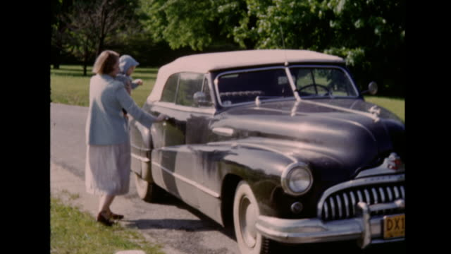 a montage of a woman getting into her 1948 convertible buick car with her baby girl. - biografi bildbanksvideor och videomaterial från bakom kulisserna