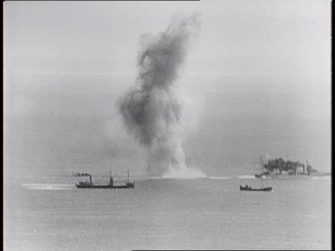 montage of alternating shots of german bombers flying and bombs explode around british convoy ships - kriegsschiff stock-videos und b-roll-filmmaterial