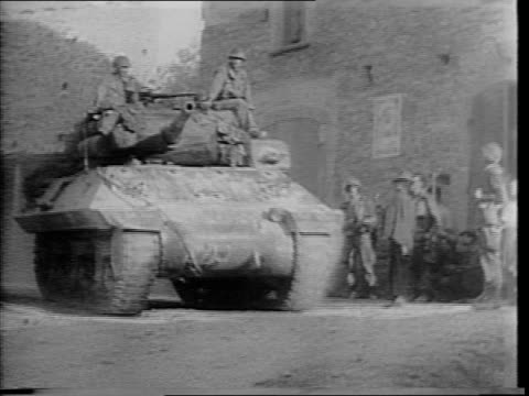 Montage of American Fifth Army driving tanks and other artillery vehicles through bombed Italian towns / soldiers walk through empty streets