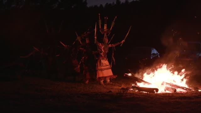 montage of apache men dancing around fire during sunrise ceremony - feierliche veranstaltung stock-videos und b-roll-filmmaterial