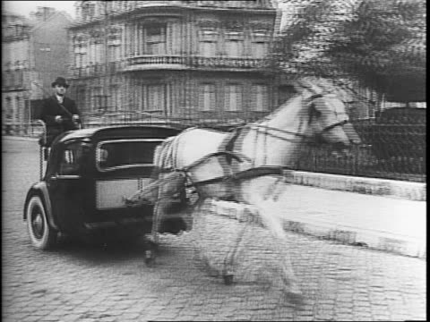 stockvideo's en b-roll-footage met montage of bicycle taxis pulling carts with two riders down the street in paris / horse drawn bus carrying passengers in front of an opera house / a... - militaire invasie