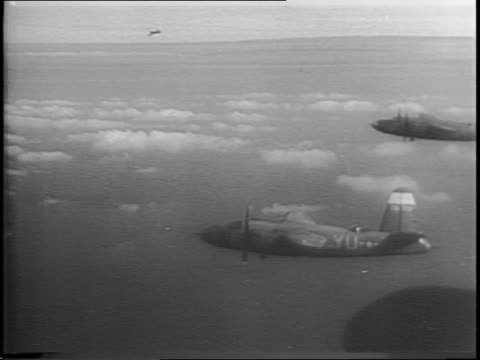vidéos et rushes de montage of bomber planes in the sky, soldier looking out plane window, aerial of mountains, bombs being dropped out of plane, group of planes... - bombardement