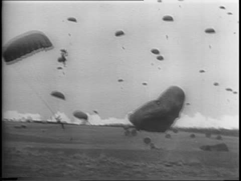 montage of c47 transport planes flying in formation dropping paratroopers / map of europe with wall around nazi germany paratroopers descending... - fallschirmjäger stock-videos und b-roll-filmmaterial