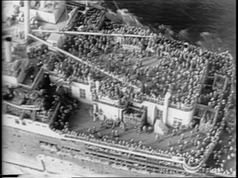 montage of captured german cruise liner europa, deck packed with troops / us marshal james malcahy signs document accepting europa as us property,... - ホームカミング点の映像素材/bロール